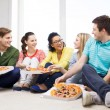 Five smiling teenagers eating pizza at home — Stock Photo #48257333