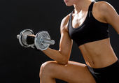 Young sporty woman with heavy steel dumbbell — Stock Photo