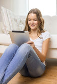 Smiling teenage girl with tablet pc at home — Stock Photo