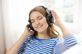 Smiling young girl in headphones at home — Stock Photo