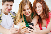 Three smiling students with smartphone at school — Stock Photo
