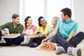 Five smiling teenagers eating pizza at home — Stock Photo