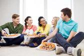 Fünf lächelnd teenager zu hause essen pizza — Stockfoto