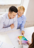 Couple looking at blueprint and color samples — Stockfoto