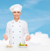 Smiling female chef with salad and cake on plates — Stock Photo