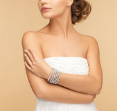 Beautiful woman with pearl earrings and bracelet — Stock Photo
