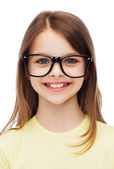 Smiling cute little girl in black eyeglasses — Stock Photo