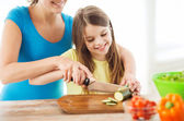 Smiling little girl with mother chopping cucumber — Stock Photo