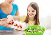 Little girl with mother adding tomatoes to salad — Stock Photo