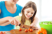 Smiling little girl with mother chopping tomatoes — Stock Photo