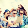 Group of smiling teenagers looking at tablet pc — Stock Photo