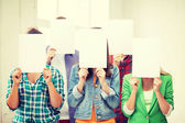 Students covering faces with blank papers — Stock Photo