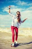 Smiling teenage girl riding skate outside — Stock Photo