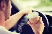 Man drinking coffee while driving the car — Stockfoto