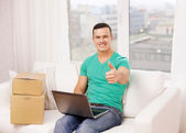 Man with laptop and cardboard boxes at home — Stock Photo
