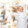 Smiling female chef showing delicious sign — Stock Photo #48636439