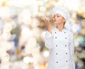Smiling female chef showing delicious sign — Stockfoto