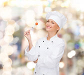 Smiling female chef with fork and tomato — Stock Photo