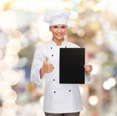 Smiling female chef with black blank paper — Stock Photo