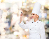Smiling female chef writing something on air — Stockfoto