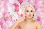 Calm young woman pointing at her cheek — Stock Photo