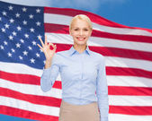 Smiling businesswoman showing ok-sign with hand — Stockfoto