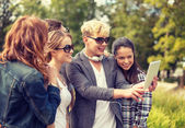 Teenagers taking photo with tablet pc outside — Stock Photo