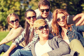 Teenagers taking photo with smartphone outside — Stockfoto