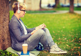 Boy with headphones, tablet pc, books and coffee — Stock Photo