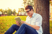 Smiling male student in eyeglasses with tablet pc — Stockfoto