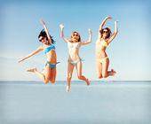 Girls jumping on the beach — Stockfoto