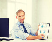 Businessman showing graphs and charts — Stock Photo