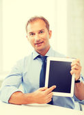 Smiling businessman with tablet pc in office — Stock Photo