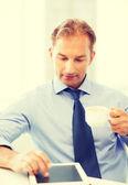 Uomo d'affari con tablet pc e caffè in ufficio — Foto Stock