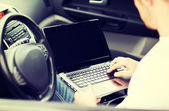 Man using laptop computer in car — 图库照片