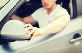 Man ajusting rear view mirror — Stock Photo