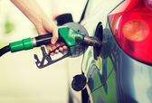 Man pumping gasoline fuel in car at gas station — ストック写真