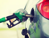 Pumping gasoline fuel in car at gas station — Stock Photo