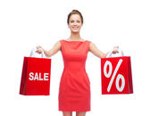 Young woman in red dress with shopping bags — Stockfoto