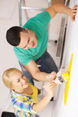 Smiling couple painting wall at home — Stock Photo