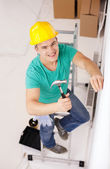 Smiling man in helmet hammering nail in wall — Stock Photo
