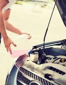 Man filling windscreen water tank — Stock Photo