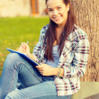 Smiling teenager writing in notebook — Stock Photo #48673745