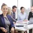 Businesswoman with glasses with team on the back — Stock Photo #48678929