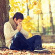 Ill man with paper tissue in autumn park — Stock Photo #48679269