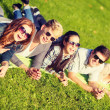 Group of students or teenagers lying in park — Stock Photo