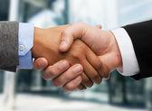 Businessman and businesswoman shaking hands — Stockfoto