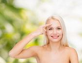 Beautiful woman touching her forehead — Stock Photo