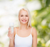 Young smiling woman with glass of water — Stock Photo