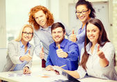 Creative team with papers showing thumbs up — Stockfoto